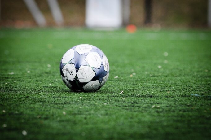 white and blue soccer ball on green grass field during daytime